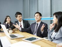 亚裔商人谈话在交涉桌上 库存图片