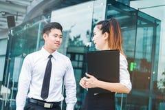 亚裔商人谈话在办公室外在工作以后 免版税库存图片