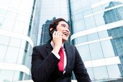 亚裔商人谈话外面与手机 免版税库存照片