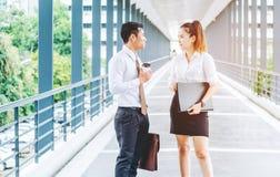 亚裔商人走和谈话在办公室外 免版税库存图片