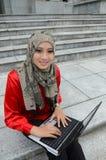 年轻亚裔回教妇女在顶头围巾海浪互联网 免版税库存照片