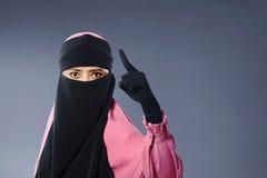 亚裔回教妇女画象面纱的与恼怒的表示 免版税库存照片