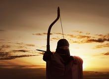 亚裔回教射击箭头的妇女佩带的hijab藏品弓 库存照片
