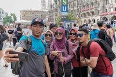 亚裔回教游人摆在步行者在慕尼黑 免版税图库摄影