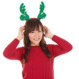 亚裔圣诞节妇女佩带的驯鹿垫铁。 免版税库存照片