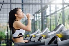 亚裔在健康的妇女饮用水 免版税库存照片