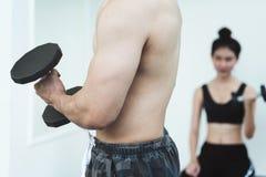 亚裔在健身房的人民举的哑铃 库存图片