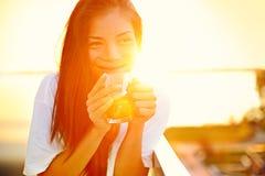 亚裔在太阳的妇女饮用的咖啡 免版税图库摄影