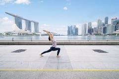 亚裔在室外的女子实践的瑜伽 免版税库存照片