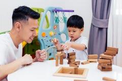 亚裔在家使用与木块的孩子和父亲在屋子里 一幼儿园和幼儿园的教育玩具 免版税库存照片