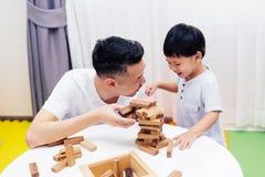 亚裔在家使用与木块的孩子和父亲在屋子里 一幼儿园和幼儿园的教育玩具 免版税库存图片