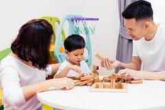 亚裔在家使用与木块的孩子和父母在屋子里 一幼儿园和幼儿园的教育玩具 免版税库存图片