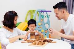 亚裔在家使用与木块的孩子和父母在屋子里 一幼儿园和幼儿园的教育玩具 库存照片