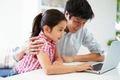 亚裔在家使用膝上型计算机的父亲帮助的女儿 库存图片