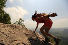 亚裔在山峰峭壁的妇女远足者上升的岩石 库存照片