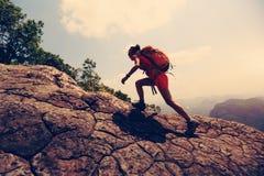 亚裔在山峰峭壁的妇女远足者上升的岩石 图库摄影