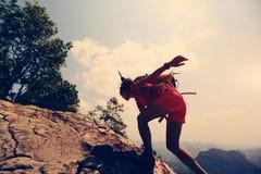 亚裔在山峰峭壁的妇女远足者上升的岩石 库存图片