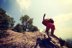 亚裔在山峰峭壁的妇女远足者上升的岩石 免版税库存照片