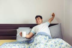 亚裔在早晨时间的人舒展的和饮用的咖啡 库存照片