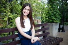亚裔在松弛时间的妇女愉快的微笑在室外 库存图片