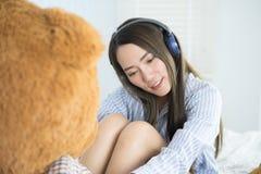 亚裔在耳机的妇女听的音乐在她的与一个大玩具熊的床上 库存图片