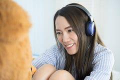 亚裔在耳机的妇女听的音乐在她的与一个大玩具熊的床上 免版税库存照片