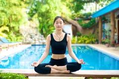 亚裔在长凳的女孩实践的瑜伽 免版税库存照片