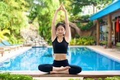 亚裔在长凳的女孩实践的瑜伽 免版税图库摄影