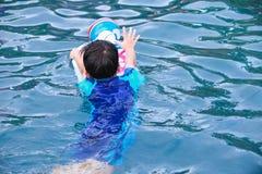 亚裔在水池的男孩和球后面看法有反撞力委员会的 室外 图库摄影
