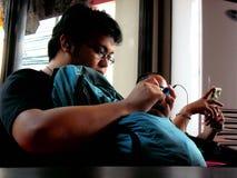 亚裔在他的智能手机的人观看的录影 库存图片