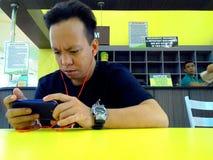 亚裔在他的智能手机的人观看的录影 免版税库存图片