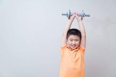 亚裔坚强的男孩举的重量, 免版税库存图片