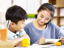 亚裔基本的女小学生和一起学习的男生 免版税图库摄影