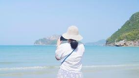 亚裔夫人拍照片在美丽的海和海滩 射击在夫人后面  股票视频