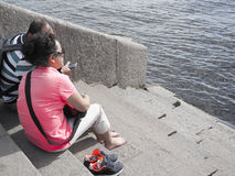 亚裔夫妇游人坐河内娃的河岸在圣彼德堡 俄国 夏天2017年 免版税库存图片