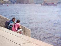亚裔夫妇游人坐河内娃的河岸在圣彼德堡 俄国 夏天2017年 免版税库存照片