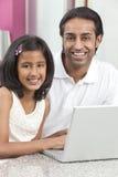 亚裔女儿父亲印第安膝上型计算机使&# 图库摄影