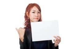 亚裔女勤杂工是在坏心情展示一个空白的标志 图库摄影