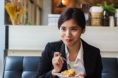 亚裔女商人放松时间和在咖啡店的吃苹果饼 免版税库存图片