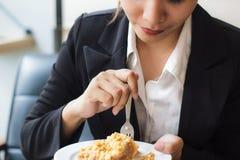 亚裔女商人放松时间和在咖啡店的吃苹果饼 免版税图库摄影