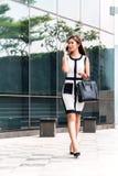 亚裔女商人谈话与手机外面 库存照片