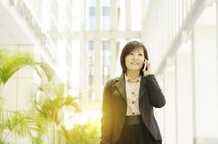 年轻亚裔女商人谈话在电话 库存照片