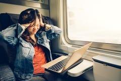 亚裔女大学生挫败与在火车的膝上型计算机,温暖的轻的口气,与拷贝空间 免版税图库摄影