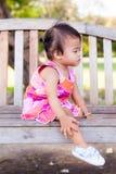 亚裔女婴坐长凳 免版税图库摄影