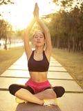 年轻亚裔女子实践的瑜伽户外在日落 库存照片