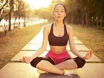 年轻亚裔女子实践的瑜伽户外在日落 免版税库存照片