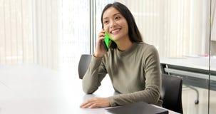 亚裔女学生微笑和获得乐趣和它也帮助分享在工作和项目的想法的使用智能手机和片剂 免版税库存图片