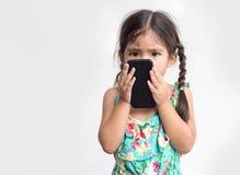 亚裔女孩上瘾者手机和对它负很接近 免版税库存照片