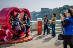 亚裔女孩为照片摆在太平山的红色心脏在香港 免版税库存照片