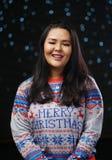 亚裔女孩佩带的圣诞节毛线衣黑暗的焕发雪背景 库存图片